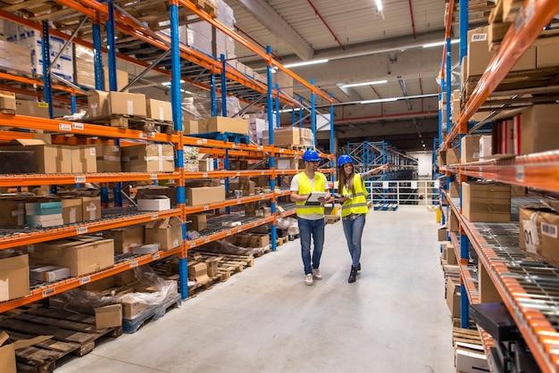 Dois trabalhadores do armazém caminhando na área de armazenamento de distribuição discutindo sobre logística e organização Foto gratuita