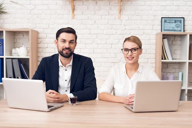 Dois trabalhadores estão sentados à mesa e trabalhando com um laptop. Foto Premium