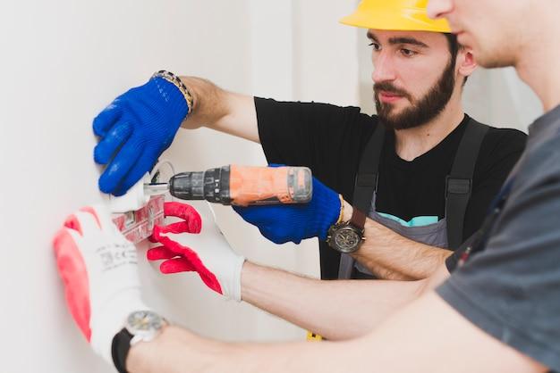 Dois trabalhadores instalando plugue de parede Foto gratuita
