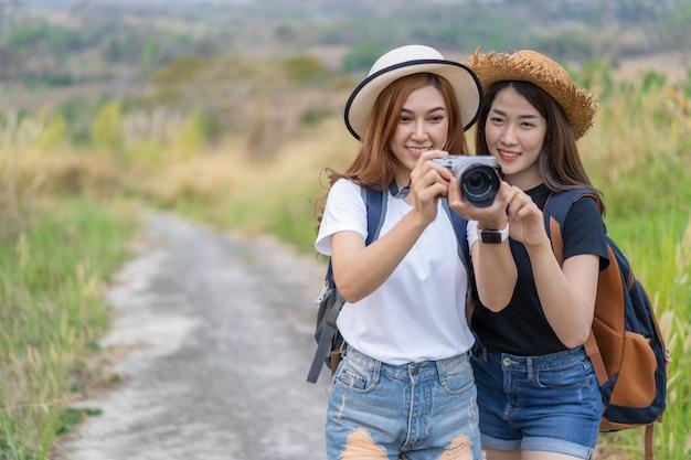 Dois turistas mulher tirando uma foto com a câmera na natureza Foto Premium