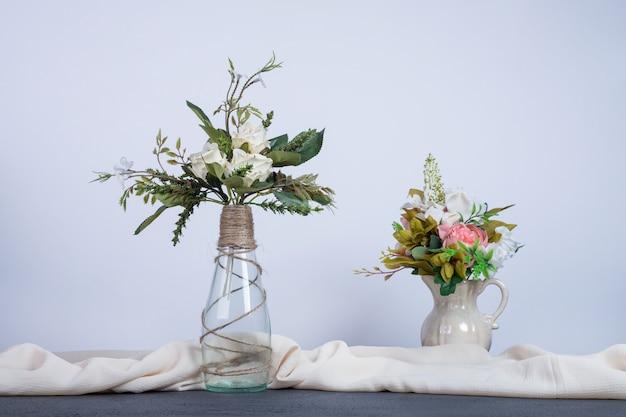 Dois vasos de flores coloridas na mesa escura. Foto gratuita