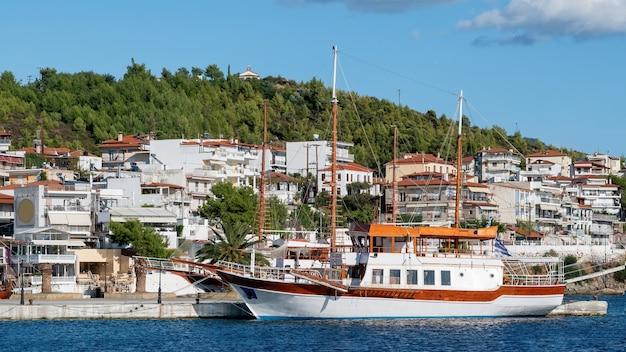 Dois veleiros atracados perto de um cais em neos marmaras, edifícios localizados em uma colina com várias áreas verdes, grécia Foto gratuita
