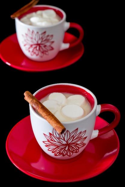 Dois, vermelho branco, copo, com, chocolate quente, e, marshmallows, ligado, um, platter, de, vermelho Foto Premium
