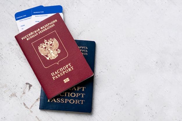 Dois viajantes passaportes russo e bielorrússia com cartões de embarque para o avião. Foto Premium