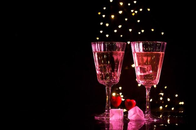 Dois vidros com um cocktail e dois corações, conceito do dia de valentim. Foto Premium