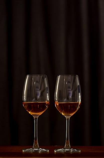 Dois vidros do vinho de rosa na tabela de madeira para comemorar para um par. Foto Premium