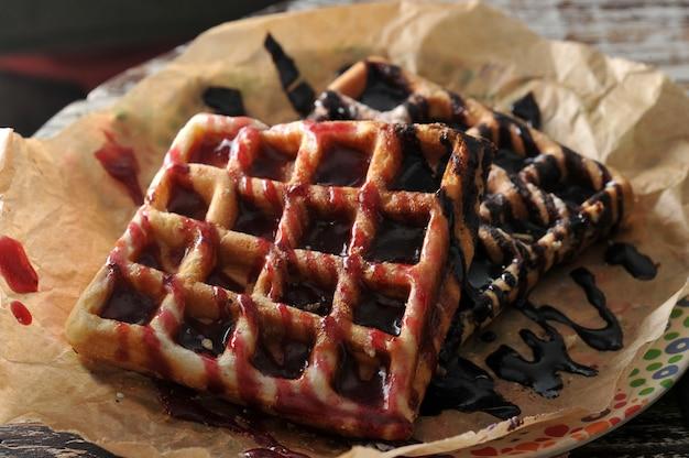 Dois waffles belgas com geléia de framboesa e chocolate Foto Premium