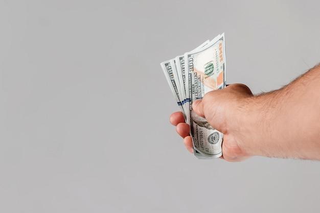 Dólares americanos em uma mão masculina Foto Premium