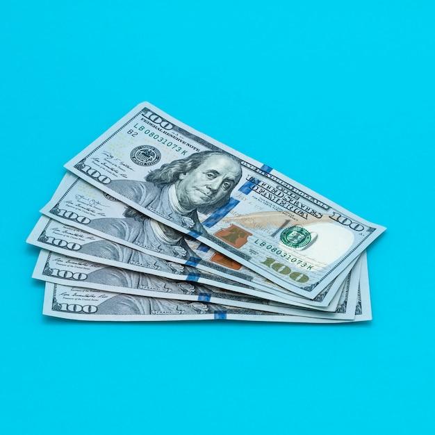 Dólares de contas de dinheiro em um fundo azul. Foto Premium