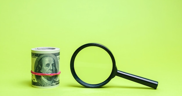 Dólares e lupa. encontrar fontes de investimento e patrocinadores. Foto Premium