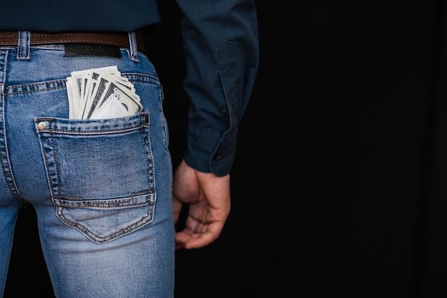 Dólares em dinheiro e um preservativo no bolso de trás dos jeans masculinos Foto Premium