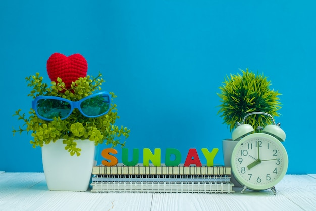 Domingo letras texto e papel de caderno, despertador e pequena árvore de decoração em madeira Foto Premium