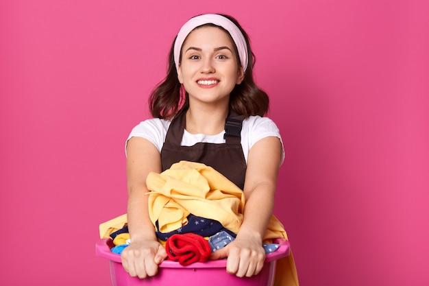 Dona de casa bonita alegre que está isolada sobre o rosa no estúdio, sorrindo sinceramente Foto Premium
