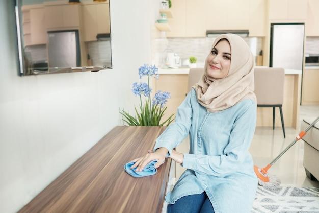 Dona de casa bonita que veste o hijab que limpa sua casa Foto Premium