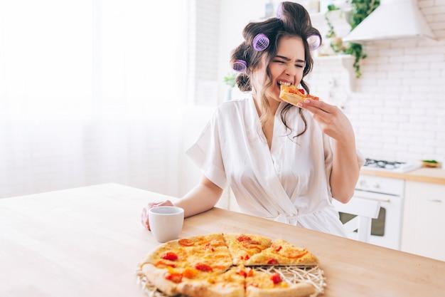 Dona de casa com fome jovem sentar na cozinha e comer pizza. morda uma fatia de comida. sozinho no quarto. governanta aproveitar a vida sem trabalho. segure o copo nas mãos. Foto Premium