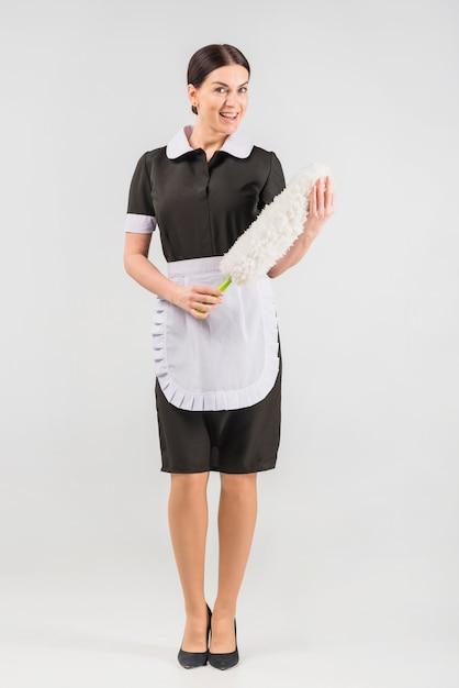 Dona de casa de uniforme com espanador sorrindo Foto gratuita