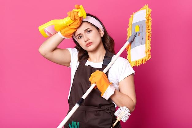 Dona de casa exuasted retrato cansada do trabalho doméstico, veste camiseta branca, avental marrom, faixa de cabelo, luvas laranja isoladas sobre parede rosa, quer descansar, relaxar. copie o espaço para a propaganda. Foto Premium