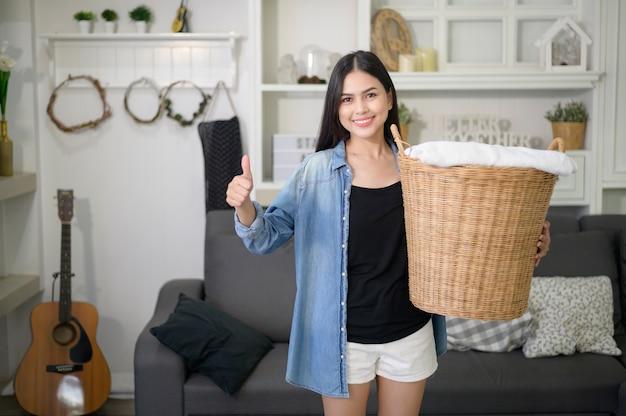 Dona de casa feliz carregando panos de balde para a roupa suja da casa Foto Premium