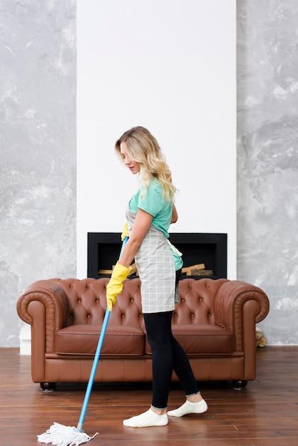 Dona de casa feminina loira limpando o chão com esfregão em casa Foto gratuita