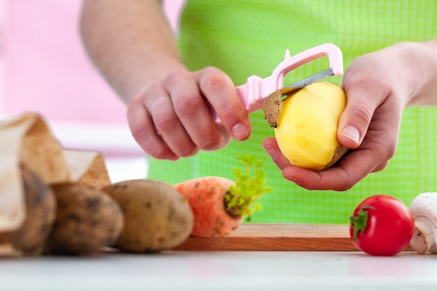 Dona de casa no avental que descasca batata madura com um descascador para cozinhar pratos de legumes frescos em casa. Foto Premium