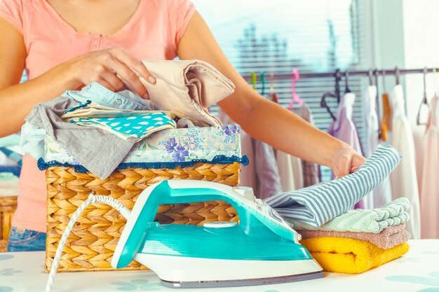 Dona de casa, trazendo uma pilha enorme de roupa na tábua de passar Foto Premium