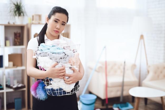 Dona de casa triste com cesta de lavanderia transbordando Foto Premium
