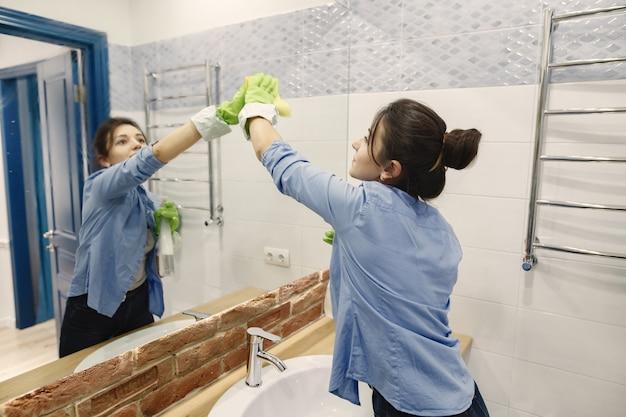 Dona de casa woking em casa. senhora com uma camisa azul. mulher em um banheiro. Foto gratuita