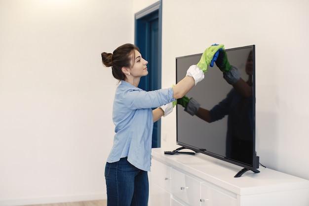 Dona de casa woking em casa. senhora com uma camisa azul. mulher limpa tv. Foto gratuita