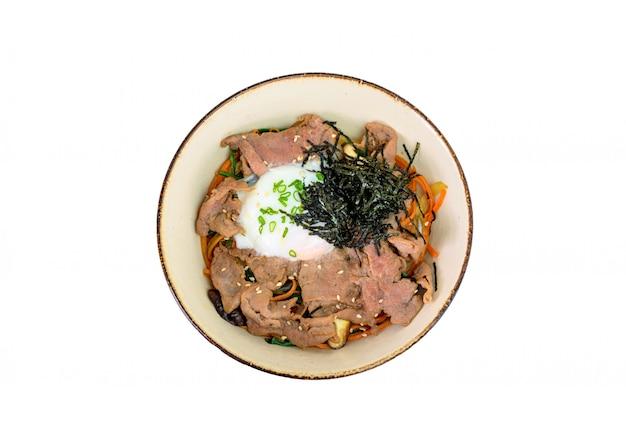 Donburi wagyu fatias de carne com ovo onsen, arroz, legumes em uma tigela de cerâmica Foto Premium