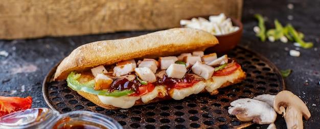 Doner de comida mista em pão baguete e queijo feta em uma placa de madeira Foto gratuita