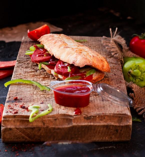 Doner de pão tandir, sucuk ekmek com salsicha em uma placa de madeira Foto gratuita