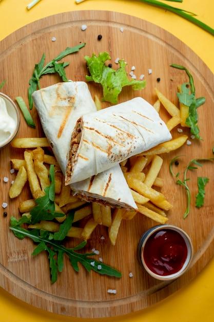 Doner embrulhado em lavash e batatas fritas Foto gratuita