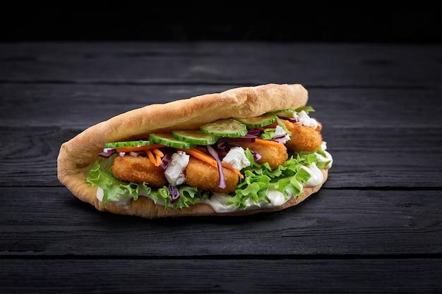 Doner kebab - carne de frango frito com legumes no pão pita Foto Premium