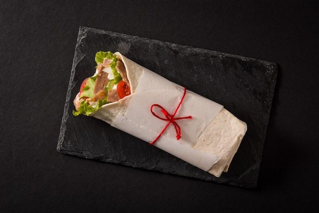 Doner kebab ou sanduíche shawarma na ardósia preta superfície vista superior. Foto Premium