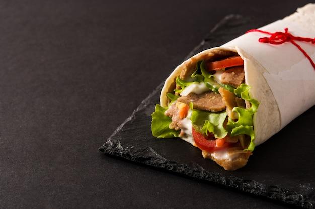 Doner kebab ou shawarma sanduíche no espaço da cópia da superfície de ardósia preta Foto Premium