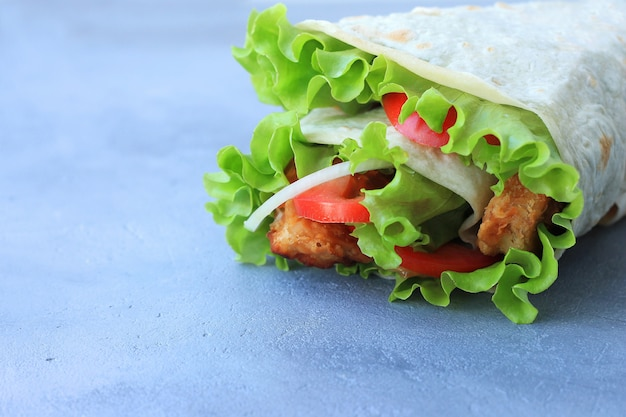 Doner kebab. shawarma com carne, cebola, salada e tomate em fundo cinza. Foto Premium