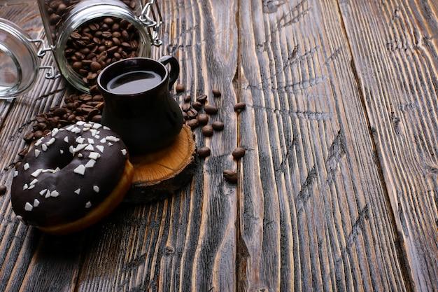 Donut com cobertura preta e pó de chocolate e uma autêntica xícara de café forte. uma lata de grãos de café e grãos derramados. Foto Premium