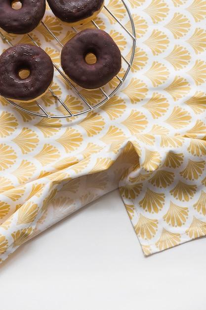 Donuts de chocolate saborosos na cremalheira do metal na toalha de mesa sobre o fundo branco Foto gratuita