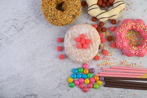 Donuts decorados glacê e granulado na vista superior de superfície branca Foto gratuita