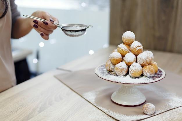 Donuts em uma bandeja polvilhada com açúcar de confeiteiro Foto Premium