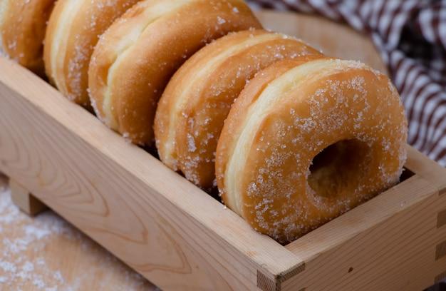 Donuts estão organizando na caixa de madeira Foto Premium