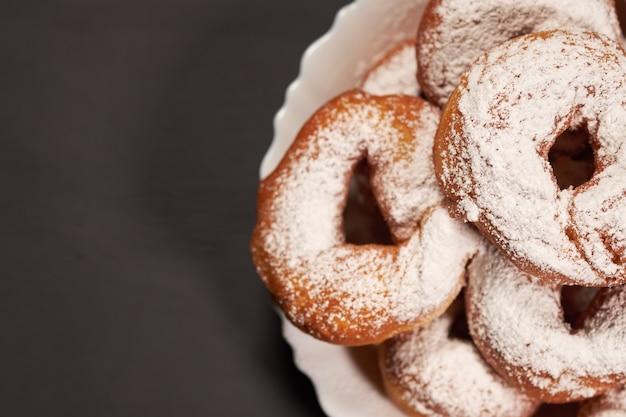 Donuts polvilhado com açúcar em pó em um prato branco Foto Premium