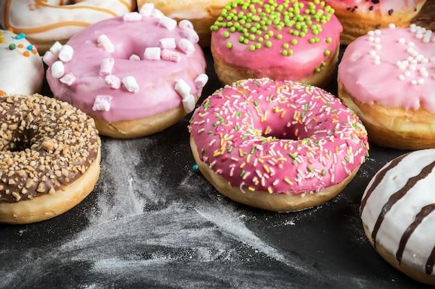 Donuts vitrificados com recheios diferentes em um preto Foto Premium