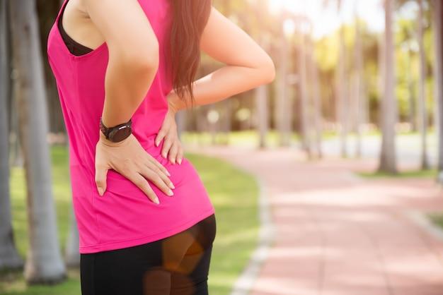 Dor da sensação da mulher nela para trás e quadril ao exercitar, conceito dos cuidados médicos. Foto Premium