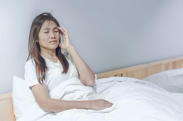 Dor de cabeça e desconforto asiáticos novos do sentimento da mulher na cama branca em seu quarto. Foto Premium