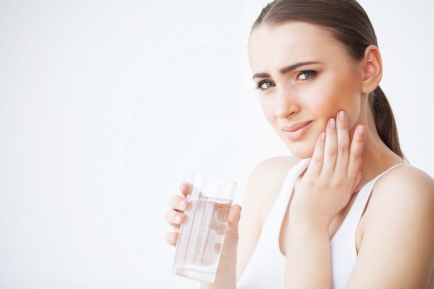 Dor de dente. mulher com dor de dente. closeup de linda garota triste, sofrendo de dor de dente forte. mulher atraente, sentindo dor de dente dolorosa. conceito de saúde e cuidados dentários Foto Premium