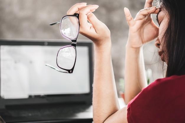 Dor de olho trabalhador mulher asiática com óculos Foto Premium