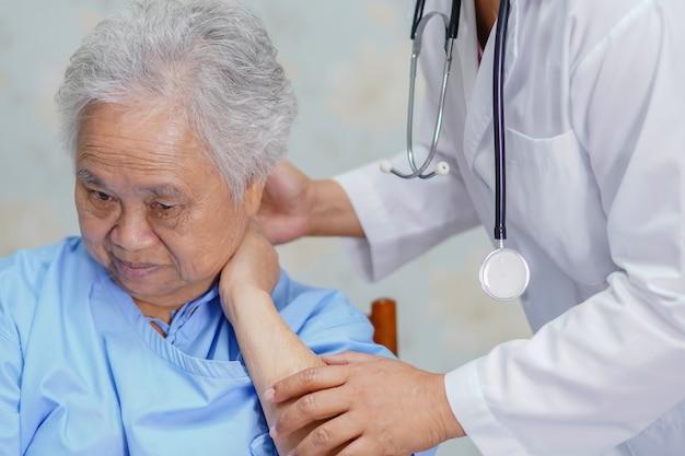 Dor de pescoço paciente da mulher sênior asiática ao sentar-se no hospital. Foto Premium