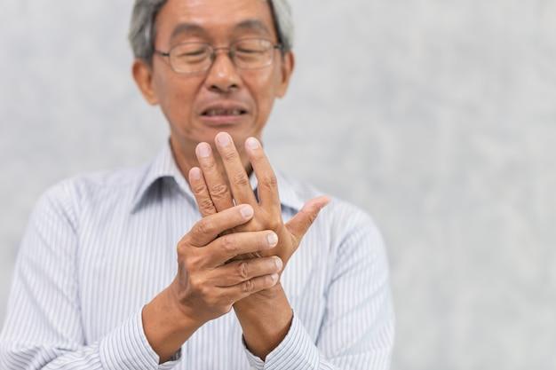Dor na mão do idoso com dedo em gatilho ou artrite reumatóide. Foto Premium