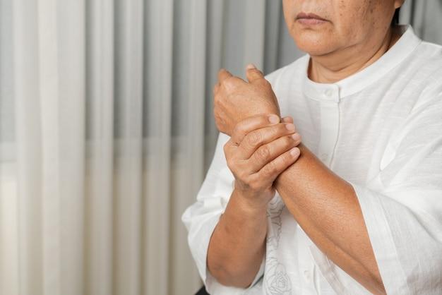 Dor na mão do pulso de uma mulher idosa, problema de saúde do conceito sênior Foto Premium